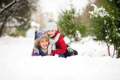 Giovane donna con la figlia della bugia di età scolare che abbraccia sulla neve Fotografia Stock Libera da Diritti