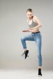 Giovane donna con la giusta gamba sollevata che esamina macchina fotografica Immagine Stock