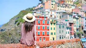 Giovane donna con la grande vista al vecchio villaggio Riomaggiore, Cinque Terre, Liguria, Italia Vacanza italiana europea video d archivio