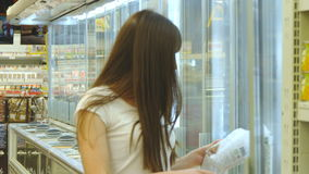 Giovane donna con la latteria d'acquisto del carrello o drogherie refrigerate al supermercato nella sezione refrigerata archivi video