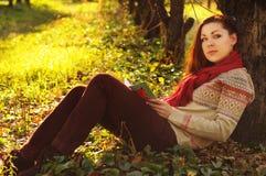 Giovane donna con la lettura rossa lunga dei capelli sotto l'albero Immagine Stock Libera da Diritti