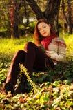 Giovane donna con la lettura rossa lunga dei capelli sotto l'albero Immagini Stock