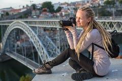Giovane donna con la macchina fotografica che si siede sulla piattaforma di osservazione di fronte al ponte di Dom Luis I attrave immagine stock