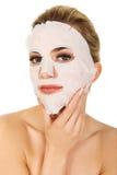 Giovane donna con la mascherina facciale Immagini Stock
