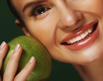 Giovane donna con la mela verde sopra fondo verde immagini stock