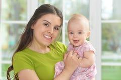 Giovane donna con la neonata a casa Immagini Stock Libere da Diritti