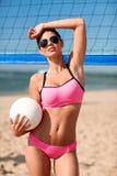 Giovane donna con la palla di pallavolo e rete sulla spiaggia Immagini Stock Libere da Diritti