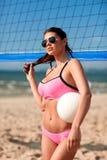 Giovane donna con la palla di pallavolo e rete sulla spiaggia Immagine Stock