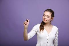 Giovane donna con la penna su fondo grigio immagine stock libera da diritti