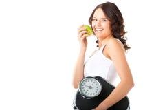 Giovane donna con la scala sotto il suoi braccio e mela Fotografie Stock