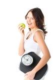 Giovane donna con la scala sotto il suoi braccio e mela Fotografia Stock