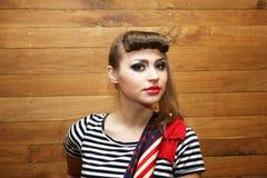 Giovane donna con la sciarpa da portare di trucco luminoso Fotografia Stock