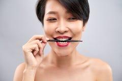 Giovane donna con la spazzola del labbro fotografia stock