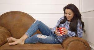 Giovane donna con la tazza sul sofà stock footage