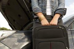 Giovane donna con la valigia accanto all'automobile rotta pronta a lasciarla fotografia stock