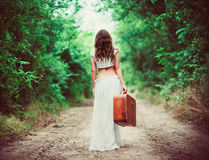 Giovane donna con la valigia a disposizione che va via dalla strada rurale immagini stock