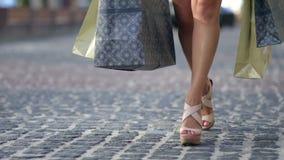 Giovane donna con la via di camminata della città dei sacchetti della spesa stock footage