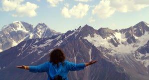 Giovane donna con le armi stese nelle montagne Il concetto di felicità, libertà, piacere Immagine Stock