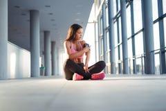 Giovane donna con le cuffie che ascolta la musica dopo l'allenamento duro Fotografie Stock