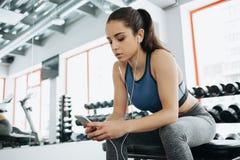 Giovane donna con le cuffie che ascolta la musica dopo l'allenamento duro in palestra Immagine Stock