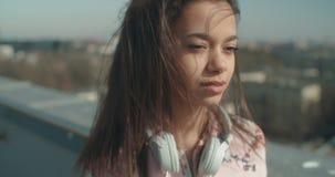 Giovane donna con le cuffie che gode del tempo su un tetto archivi video