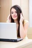 Giovane donna con le cuffie ed il computer portatile Fotografia Stock Libera da Diritti