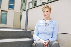 Giovane donna con le cuffie sulle scale Fotografia Stock Libera da Diritti