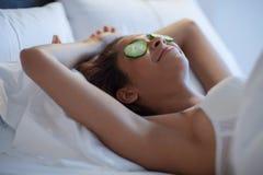 Giovane donna con le fette del cetriolo a letto Fotografie Stock Libere da Diritti