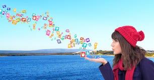giovane donna con le icone dell'applicazione di salto del cappello dalle sue mani davanti al mare ed alle montagne Immagini Stock