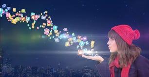 giovane donna con le icone dell'applicazione di salto del cappello dalle sue mani davanti alla città alla notte Fotografia Stock Libera da Diritti