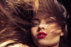 Giovane donna con le labbra rosse ed i capelli scorrenti Fotografie Stock