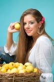 Giovane donna con le mele che esaminano macchina fotografica Immagini Stock