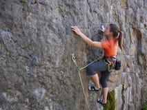 Giovane donna con le salite della corda sulla roccia Fotografia Stock Libera da Diritti