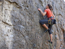 Giovane donna con le salite della corda sulla roccia Immagine Stock