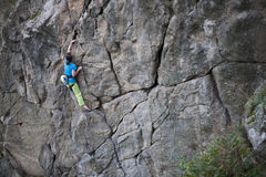 Giovane donna con le salite della corda sulla roccia Fotografia Stock