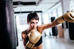 Giovane donna con lo sguardo serio nei guanti gialli di pugilato d'allenamento che combatte all'interno Immagine Stock
