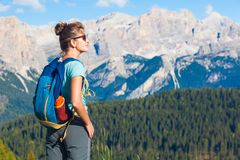 Giovane donna con lo zaino che fa un'escursione ad Alta Badia, dolomia, Italia fotografia stock libera da diritti