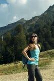 Giovane donna con lo zaino che fa un'escursione nelle montagne Fotografie Stock
