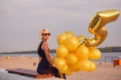 Giovane donna con molti palloni dorati Fotografie Stock