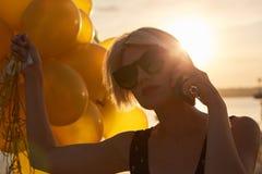 Giovane donna con molti palloni dorati Immagine Stock