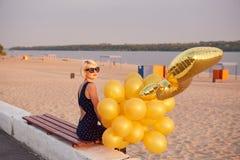 Giovane donna con molti palloni dorati Immagini Stock Libere da Diritti