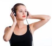 Giovane donna con musica d'ascolto delle cuffie Fotografie Stock