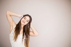 Giovane donna con musica d'ascolto delle cuffie Dancing della ragazza dell'adolescente di musica contro isolato Fotografia Stock Libera da Diritti