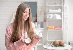 Giovane donna con olio di cocco per capelli Immagini Stock