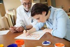 Giovane donna con professore che studia pittura decorativa Immagini Stock