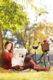 Giovane donna con seduta e la lettura della bicicletta un giornale in un PA Fotografie Stock Libere da Diritti