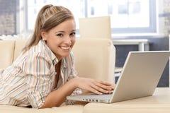 Giovane donna con sorridere del computer portatile Immagini Stock Libere da Diritti