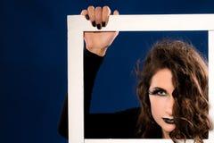 Giovane donna con trucco nero aggressivo fotografia stock libera da diritti