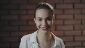 Giovane donna con trucco perfetto che sorride sul fondo del muro di mattoni archivi video