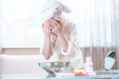 Giovane donna con un asciugamano sul suo fronte lavante capo con acqua di mattina Igiene e cura per la pelle a casa fotografia stock libera da diritti